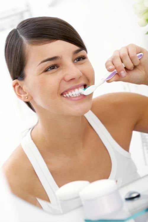 kobieta szczotkująca zęby przed lustrem