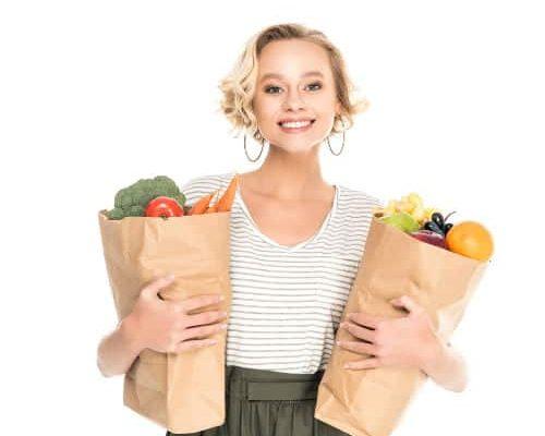 kobieta z torbami zakupowymi z owocami i warzywami