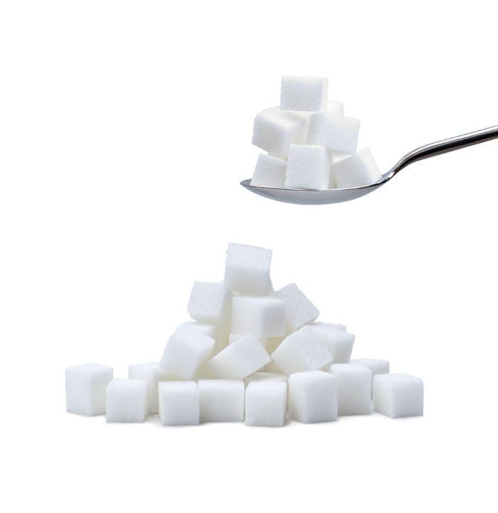 łyżka z kostakami cukru a pod nią kupka kostek cukru