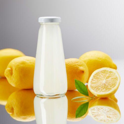 sok z cytryny w szklanej butelce i świeże cytryny