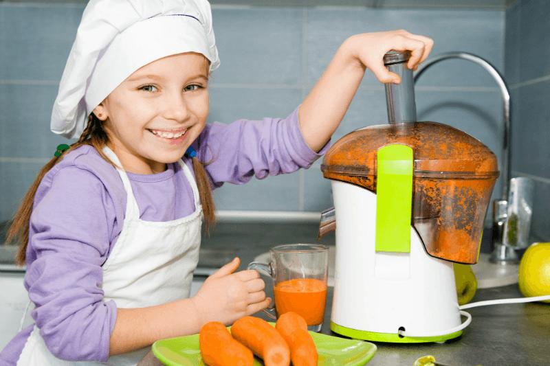 dziewczynka wyciska sok z sokowirówki